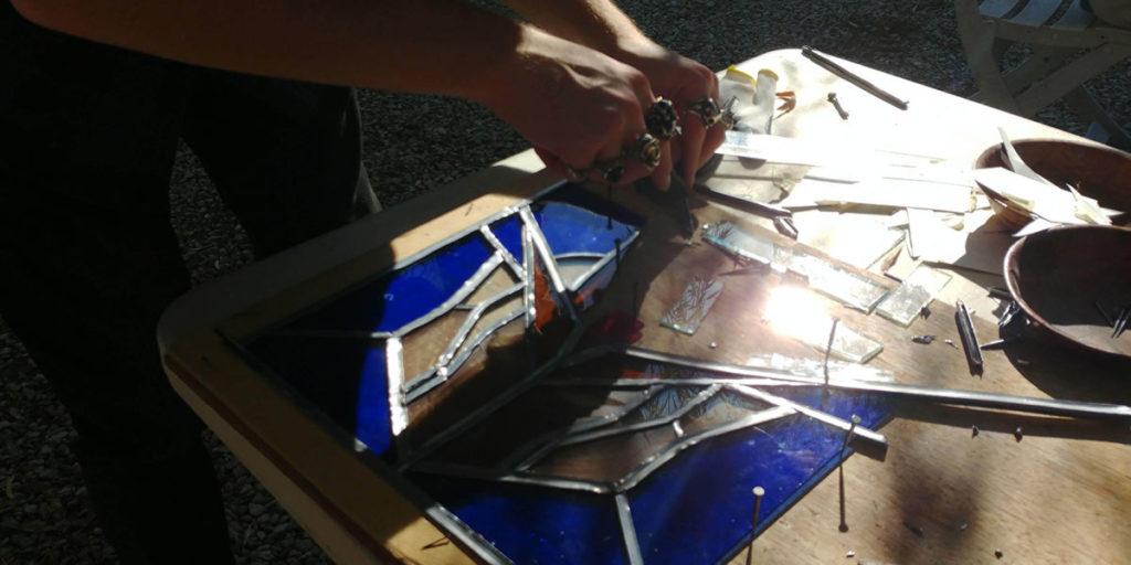 Travail de montage par Guillaume, un stagiaire lors d'un stage de vitrail à l'Atelier du Marai